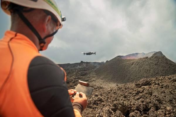 Homme pilotant le drone ANAFI Themal devant un volcan